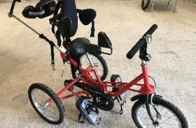 A red Tomcat 3-point trike with full seat and backrest
