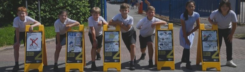 Seven pupils from St Mary's primary school stand in a row smiling with their winning parking sign designs