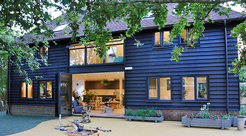 A contemporary barn conversion project. The wood-clad property has large windows to flood the modern interior with light