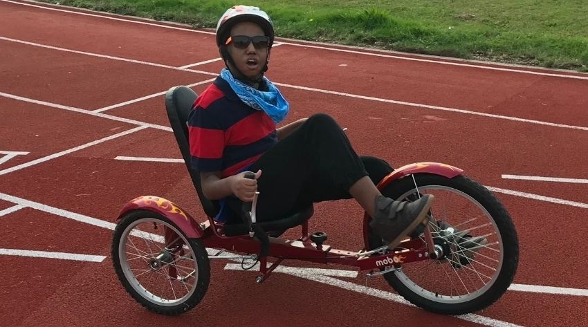 Alazar at a Wheels for All session on a bike wearing a stripy top, bike helmet and sunglasses