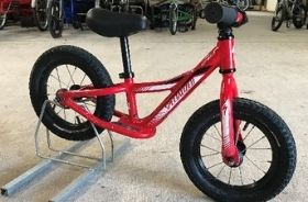 A red two-wheeled balance bike with no pedals