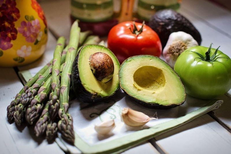 Asparagus, avocado, tomatoes and garlic on a chopping board