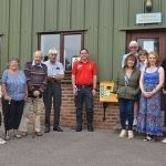 Roundstone residents, the site manager and Cllr Claire Vickers gather at the new defibrillator