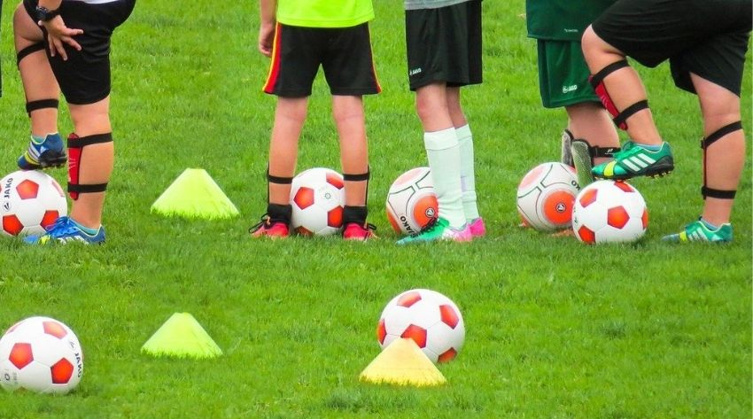 Four children in shinpads and shorts stand with footballs and cones