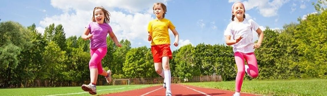 Three smiling children run on a running track