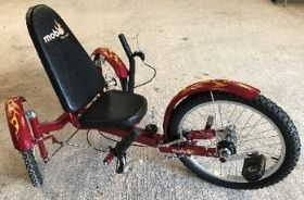 A red recumbent trike. The rider sits in the seat leaning against the backrest and uses the pedals on the front wheel to power the bike. The handlebars are either side of the seat