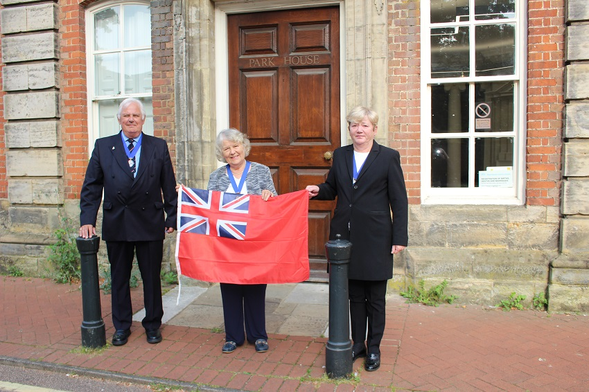 Cllr Peter Burgess Armed Forces Champion Vice Chairman Kate Rowbottom and Cllr Karen Burgess with the Red Ensign flag