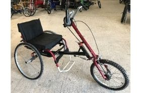 A red hand-powered trike with full seat