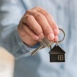 A hand holds a set of silver house keys