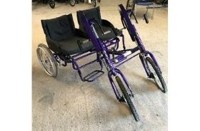 A purple hand-powered tandem trike for two riders in full seats