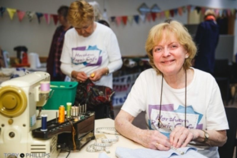 A member of Horsham Repair Cafe sits with a sewing machine
