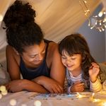 A woman and child in a den with fairy lights, smiling together