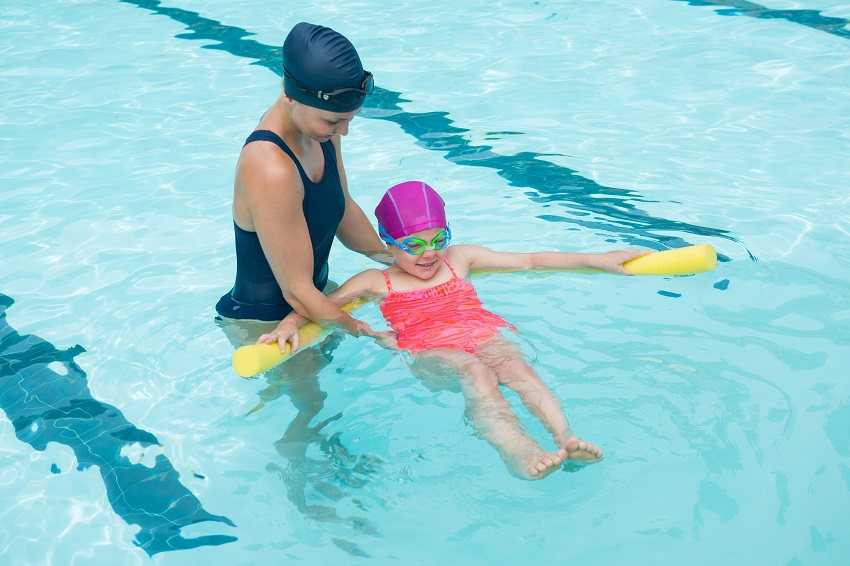 A swimming instructor helps a girl to swim on her back with a yellow pool noodle