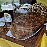 A loaf of seeded bread with orange marmalade on a vintage tray in Model Bakery's window